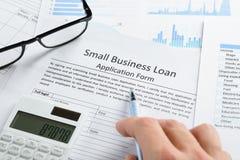Hand met pen en calculator op leningstoepassing Stock Afbeeldingen