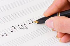 Hand met pen en muziekblad Stock Afbeelding