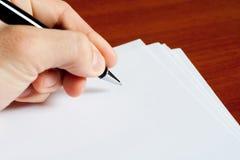 Hand met pen op het document Royalty-vrije Stock Fotografie