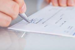 Hand met pen over checkbook stock foto's
