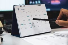 Hand met penpunt op kalenderpagina stock foto's