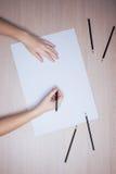 Hand met potlood die op Witboekblad schrijven Stock Afbeelding