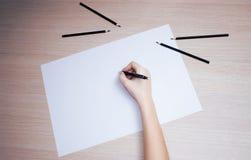 Hand met potlood die op Witboekblad schrijven Stock Foto's