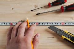 Hand met potlood en het meten van band die tekens maken royalty-vrije stock afbeelding
