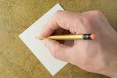 Hand met potlood en stuk van blad stock afbeelding