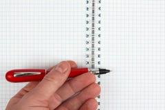 Hand met rode pen over een open notitieboekje royalty-vrije stock foto