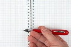 Hand met rode pen over een open notitieboekje stock fotografie