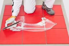 Hand met rubbertroffel die pleistertegel toepast Stock Foto