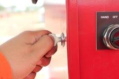 Hand met sleutel in paneel voor bij de vermogenssturing Royalty-vrije Stock Afbeeldingen