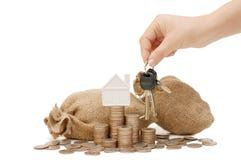 Hand met sleutels, het huis en de muntstukken Stock Afbeeldingen