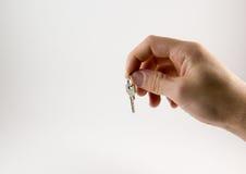 Hand met sleutels op een witte achtergrond Stock Afbeelding
