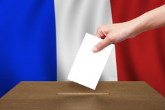 Hand met stemming en houten doos op Vlag van Frankrijk Stock Afbeeldingen