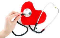 Hand met stethoscoop die een rood hart controleert Royalty-vrije Stock Foto
