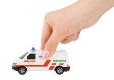 Hand met stuk speelgoed ziekenwagenauto Royalty-vrije Stock Afbeeldingen