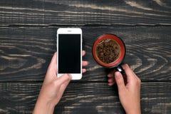 Hand met telefoon op een houten achtergrond Stock Foto's