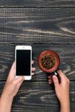 Hand met telefoon op een houten achtergrond Royalty-vrije Stock Afbeelding