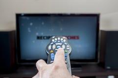 Hand met TV-afstandsbediening Stock Foto