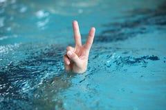 Hand met twee vingers omhoog in het overwinning of vredessymbool, hierboven - water Royalty-vrije Stock Fotografie