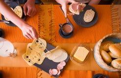 Hand met vork en plaat met kaas stock afbeelding