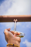 Hand in metal chains against the blue sky. Royalty Free Stock Images