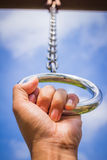 Hand in metal chains against the blue sky. Royalty Free Stock Photography