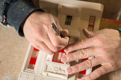 Hand with Metal Object Working on Plaster Scale Model Building Royalty Free Stock Photo