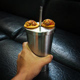 Hand on Metal thermos with snacks on black background texture Stock Photos