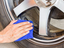 Hand with microfiber cloth cleaning wheel Royalty Free Stock Photo