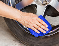 Hand with microfiber cloth cleaning wheel car Royalty Free Stock Images