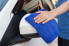 Hand with microfiber cloth cleaning wing mirror car Royalty Free Stock Photo