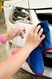Hand with microfiber cloth wiping a car with spray wax. Hand with microfiber cloth wiping a car surface with spray wax Royalty Free Stock Photos