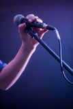 Hand with microphone on a black background, the music concept, beautiful lighting on the stage. Closeup Stock Image