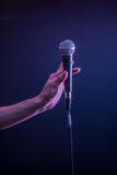 Hand with microphone on a black background, the music concept, beautiful lighting on the stage. Closeup Stock Photography