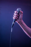 Hand with microphone on a black background, the music concept, beautiful lighting on the stage. Closeup Stock Images