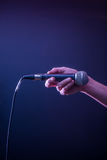 Hand with microphone on a black background, the music concept, beautiful lighting on the stage. Closeup Royalty Free Stock Photos
