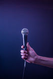 Hand with microphone on a black background, the music concept, beautiful lighting on the stage. Closeup Stock Photo