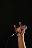 Hand with microphone and devil horns isolated on black Royalty Free Stock Image