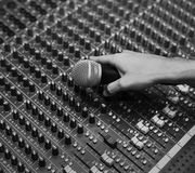 Hand with microphone on a sound mixer grayscale Royalty Free Stock Images