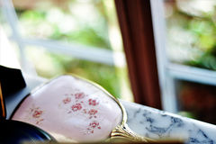Hand Mirror. Antique hand mirror with cherry blossom artwork painted on the backing Stock Photos