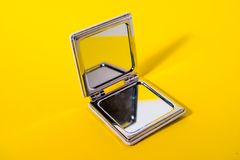 Hand mirror on  yellow background royalty free stock image