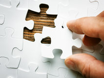 Hand with missing jigsaw puzzle piece. Business concept image for completing the final puzzle piece. Wooden background Stock Image