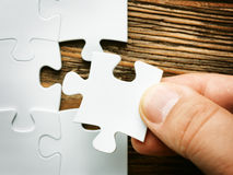 Hand with missing jigsaw puzzle piece. Business concept image for completing the final puzzle piece. Wooden background Stock Photography