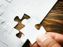 Hand with missing jigsaw puzzle piece. Business concept image for completing the final puzzle piece. Wooden background Stock Illustration