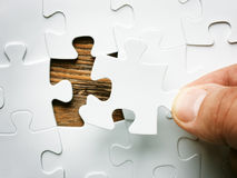 Hand with missing jigsaw puzzle piece. Business concept image for completing the final puzzle piece. Wooden background Stock Photos