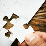 Hand with missing jigsaw puzzle piece. Business concept image for completing the final puzzle piece. Royalty Free Stock Image