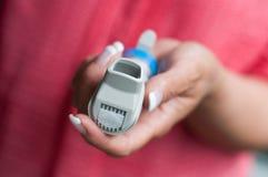 Hand mit Asthmaaerosol Stockfoto