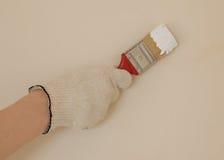 Hand mit Bürste in der weißen Farbe Lizenzfreie Stockfotos