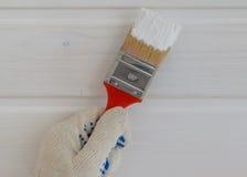 Hand mit Bürste in der weißen Farbe Lizenzfreies Stockbild