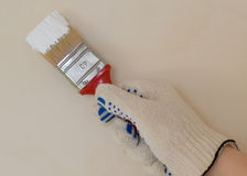 Hand mit Bürste in der weißen Farbe Lizenzfreie Stockfotografie
