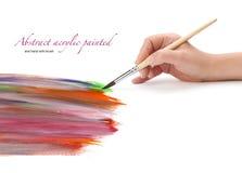 Hand mit Bürste und Acryl gemaltem Hintergrund Lizenzfreies Stockfoto